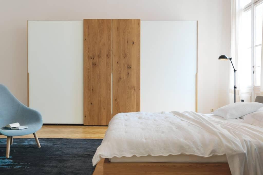 Schwebetürenschrank Nox in Eiche und Türen in Farbglas weiß.