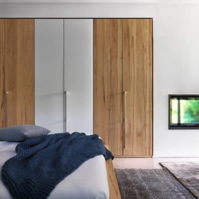 Kleiderschrank Soft in Kernbuche mit 6 Türen und Farbglas weiß.